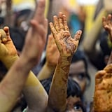 Children raised their hands smeared with natural colors from vegetable paste after Holi celebrations at a city civic school in Mumbai, India.