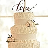 """Lavender sprigs and pale-pink roses look soft and sweet in this """"love""""-topped wedding cake."""