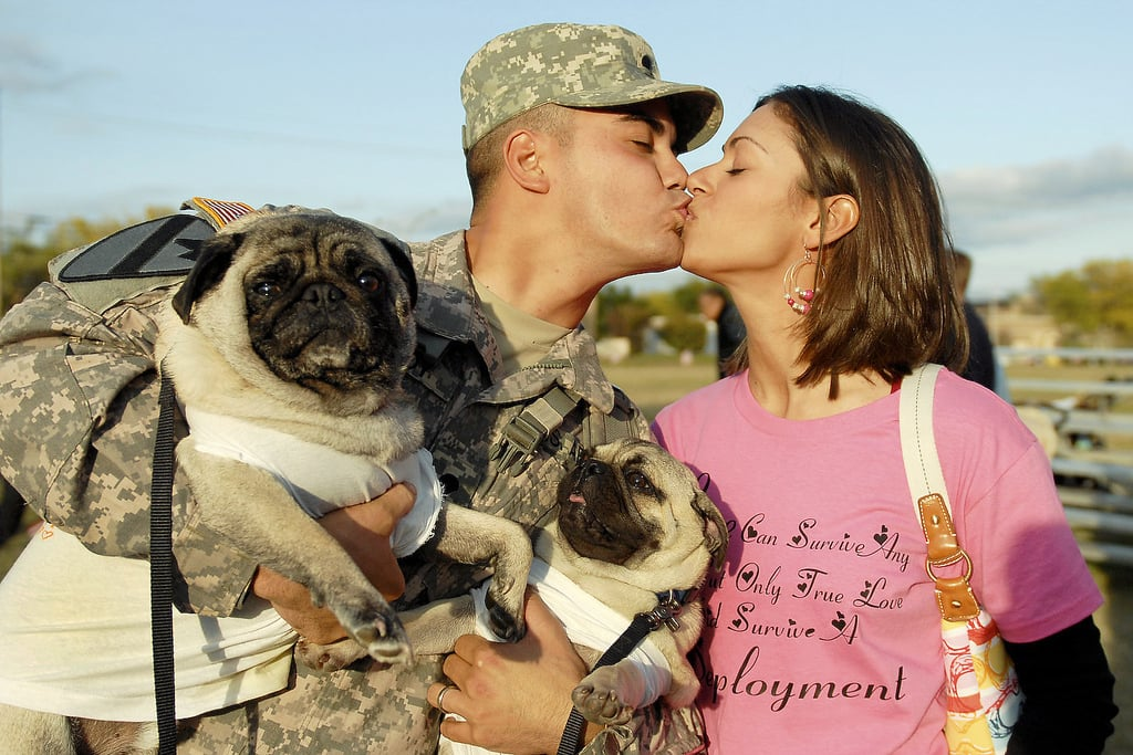 Army Spc. Leo Leroy gets a kiss from Regina Leroy and maybe some licks from dogs Yoshi and Bruiser at Fort Hood, TX, on Nov. 28, 2009.