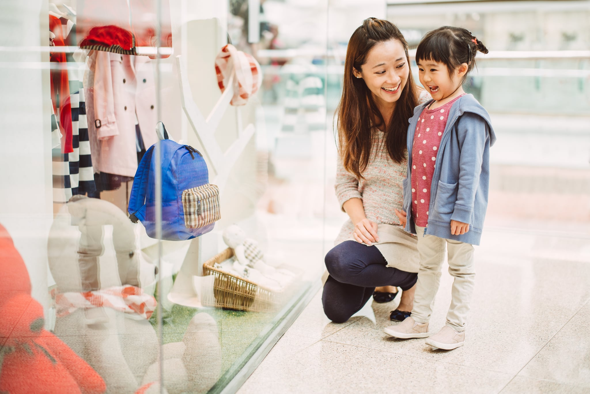 Pretty young mom and lovely little daughter looking at window display for kids wears in a shopping mall joyfully.