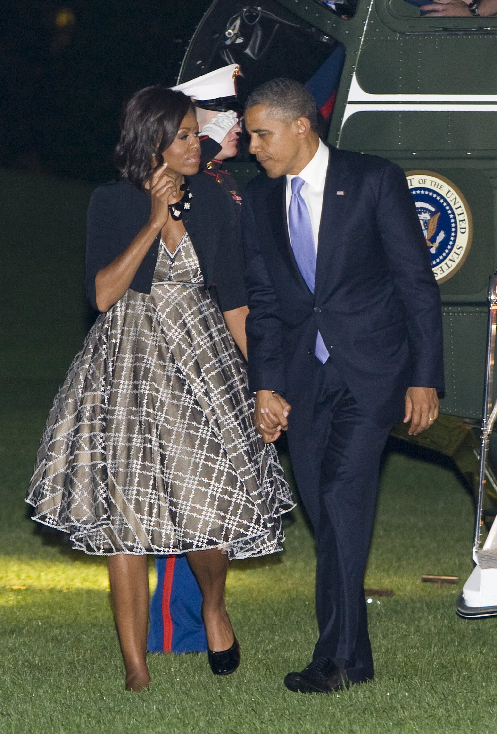 Arriving back at the White House, Michelle was spotted in an olive, tartan-inspired circle dress with a black cardigan.