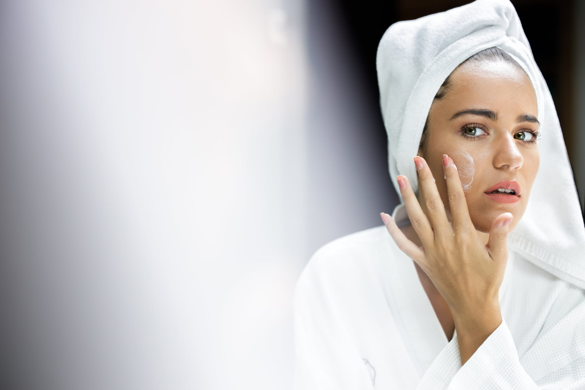 Reflection in a mirror of a woman wrapped in a towel applying face cream in a bathroom. Copy space.