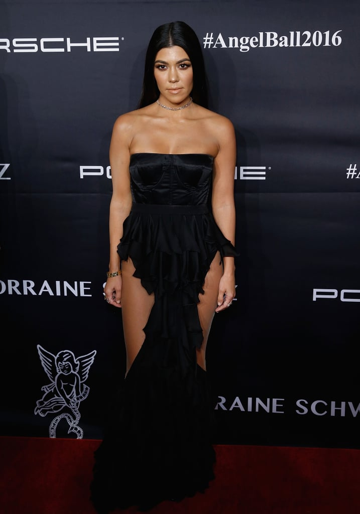 At An Event Wearing A Strapless Black Gown With Sheer Panels