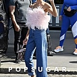 Even exiting her hotel was cause for a statement-making outfit; this one included a feathered Attico confection on top and a pair of asymmetrical jeans, paired with cat-eye shades and a Fendi handbag.