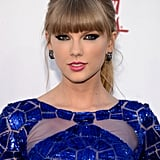 Taylor Swift stuck to what works best for her: thick black and blue liner, blunt bangs, and a bold pink lipstick shade.