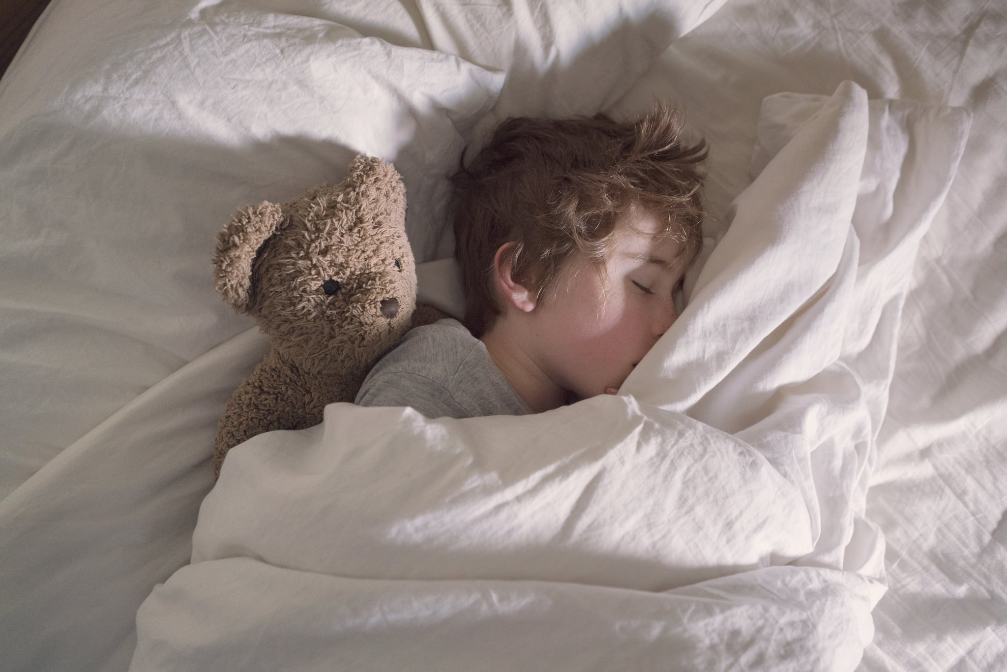 A boy sleeping alone in his parent's bed with his teddy bear.