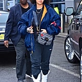 In 2017, Rihanna was spotted outside JFK Airport in an Alpha Industries jacket, baggy pants, white boots, and white sunglasses. She wore a Dior crossbody bag.