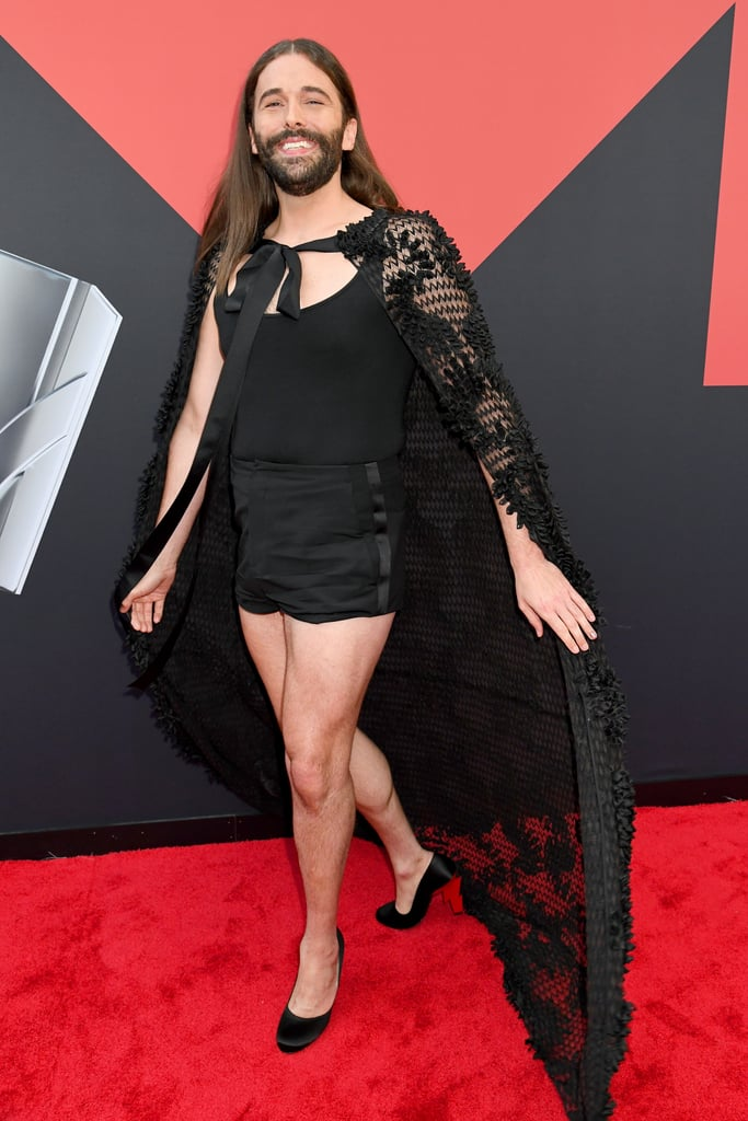Can you handle the CON-FI-DONCE? Jonathan Van Ness was a vision in black at the MTV VMAs red carpet on Aug. 26, and his lacy organza cape is giving me major Maleficent vibes. The 32-year-old Queer Eye star was ready for a night out in a figure-hugging black romper and a matching floor-length cape reminiscent of dragon scales — Khaleesi is shaking. Jonathan paired the Atelier by FANG cape, with a pair of Prada lightning bolt satin pumps, and I have a feeling Tan France would definitely approve. Keep reading for a closer look at Jonathan's beguiling red carpet outfit.       Related:                                                                                                           Lizzo Was Feeling Herself at the MTV VMAs, and We Wouldn't Want It Any Other Way