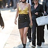 Kendall Jenner made her yellow silk camisole appropriate for the day by tucking it into a structured miniskirt and accessorizing with a choker and black booties.