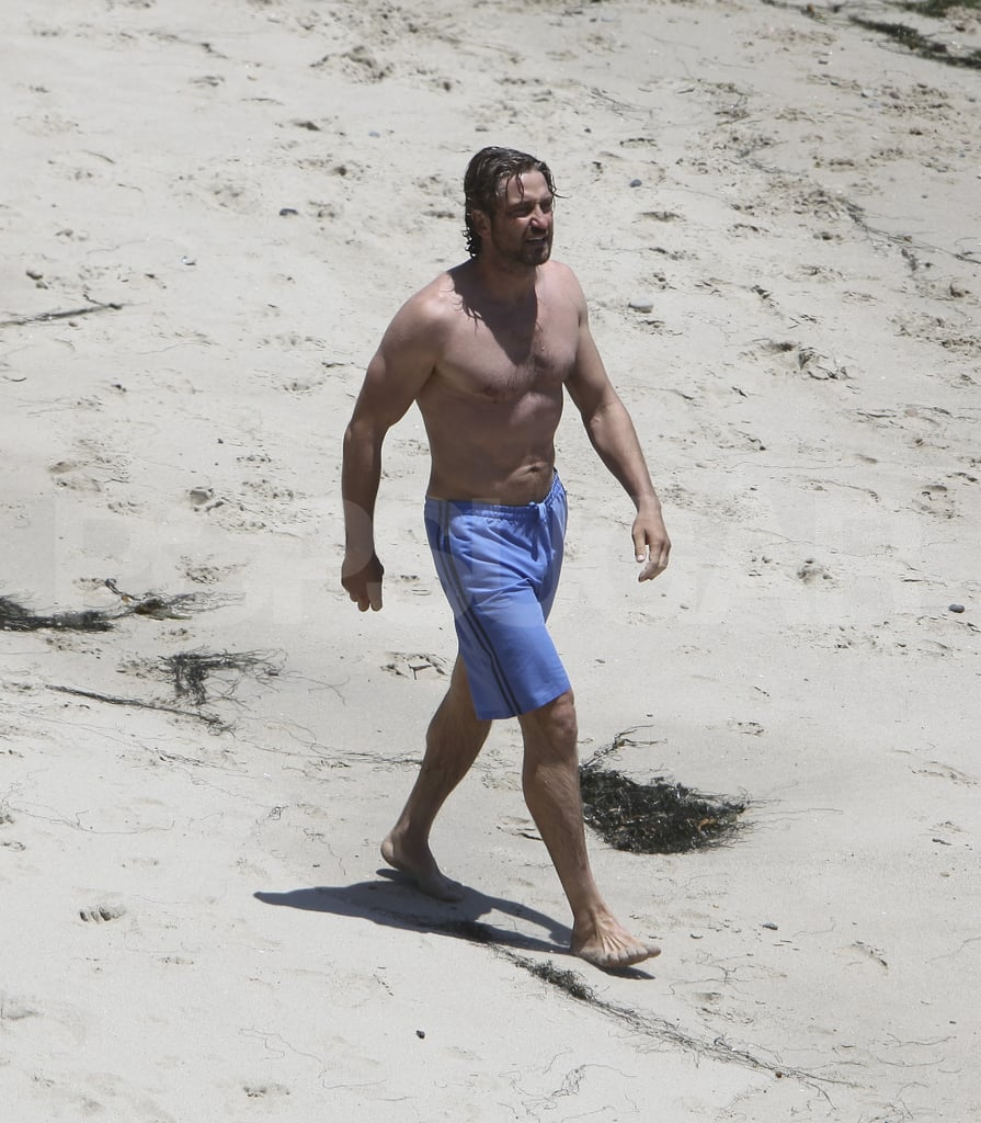 Gerard Butler walks on the beach.