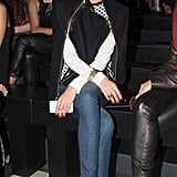 Olivia Palermo layered up in a geometric-print sweater, dual-zipper cape, Paige Premium denim, and red printed pumps while sitting front row at Sass & Bide.