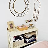 My trick for a makeshift bedside table? Try a console table at the foot of your bed. Chances are there's not much room to move around there anyway, so why not fill it with furniture to store your belongings instead.