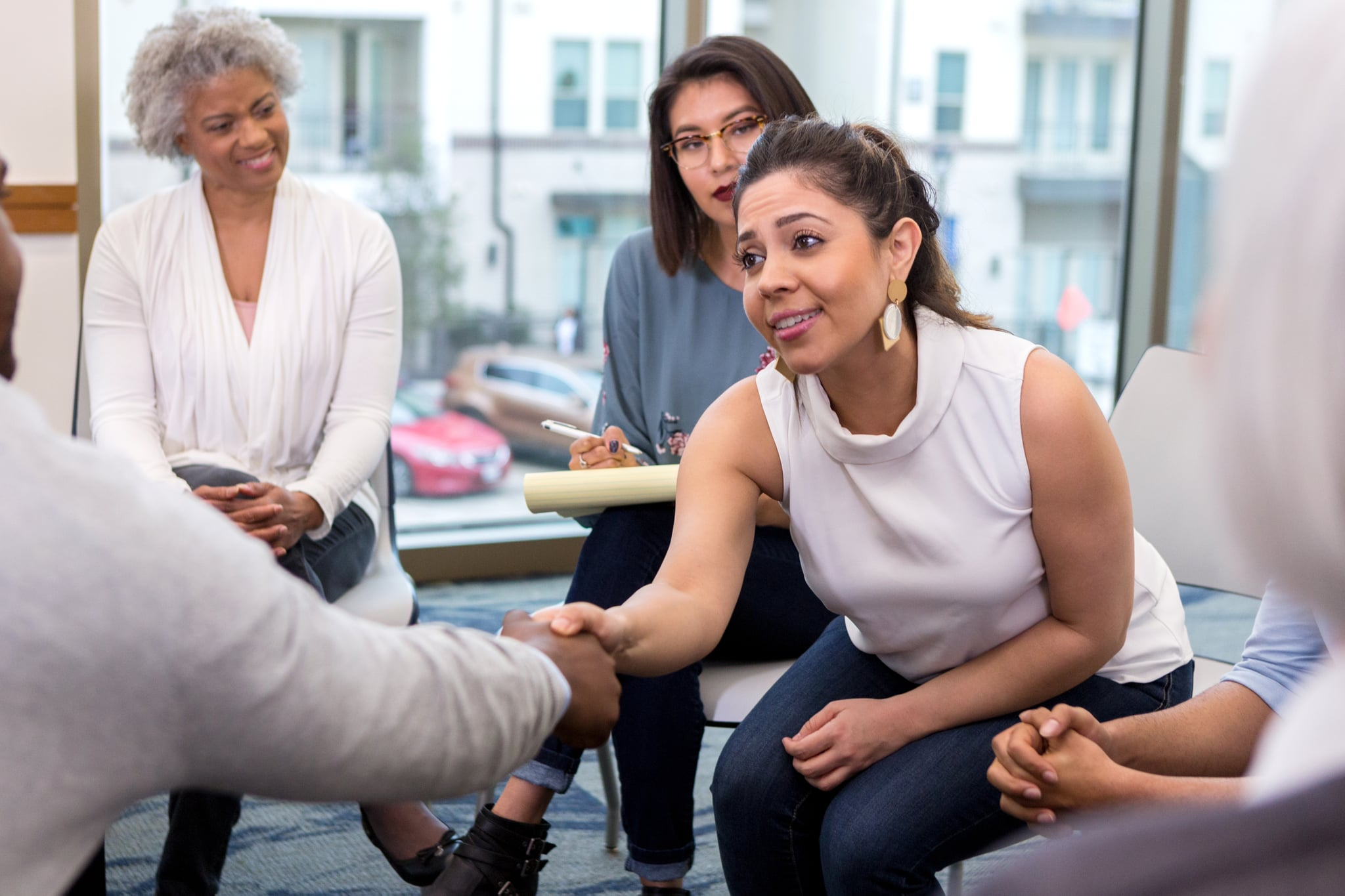 A serious young businesswoman sits with colleagues and reaches forward to shake hands with an unseen new client.