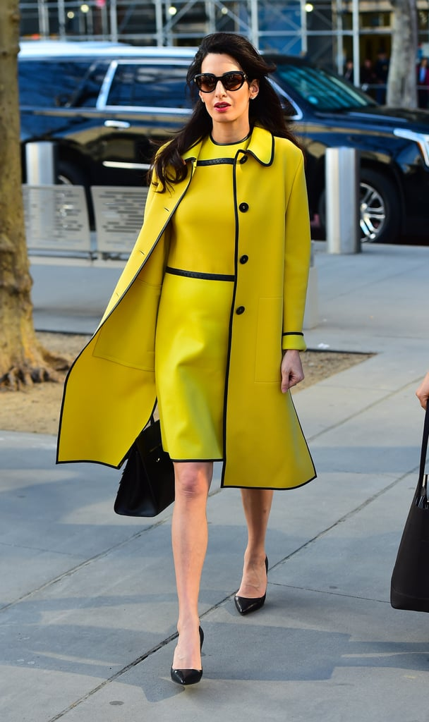 Amal took a trip to the United Nations wearing a yellow Bottega Veneta coat and dress with leather piping. She completed the look with a Salvatore Ferragamo bag, black pumps, dark sunglasses, and diamond studs.