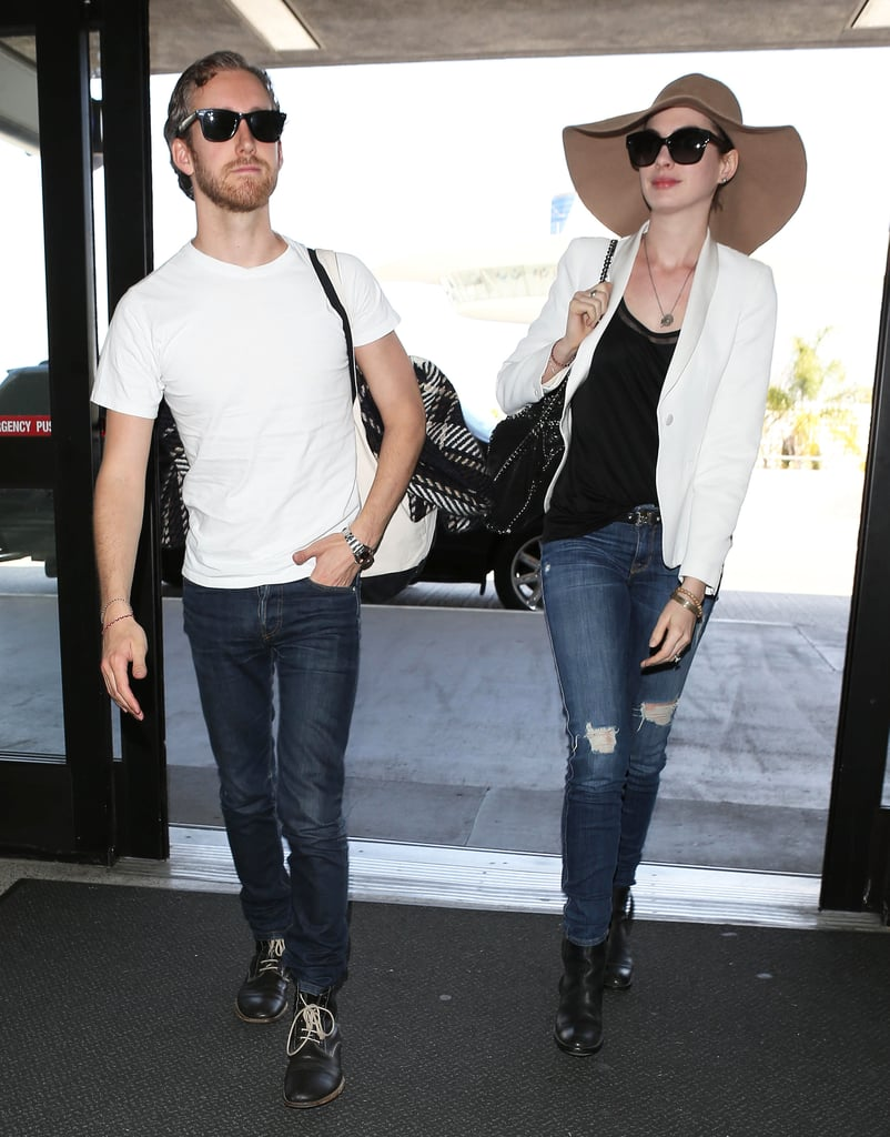 Anne Hathaway created a Springy travel ensemble with a white tuxedo blazer, ripped skinny jeans by Genetic Denim, and a big floppy hat on her way to catch a flight at LAX airport.