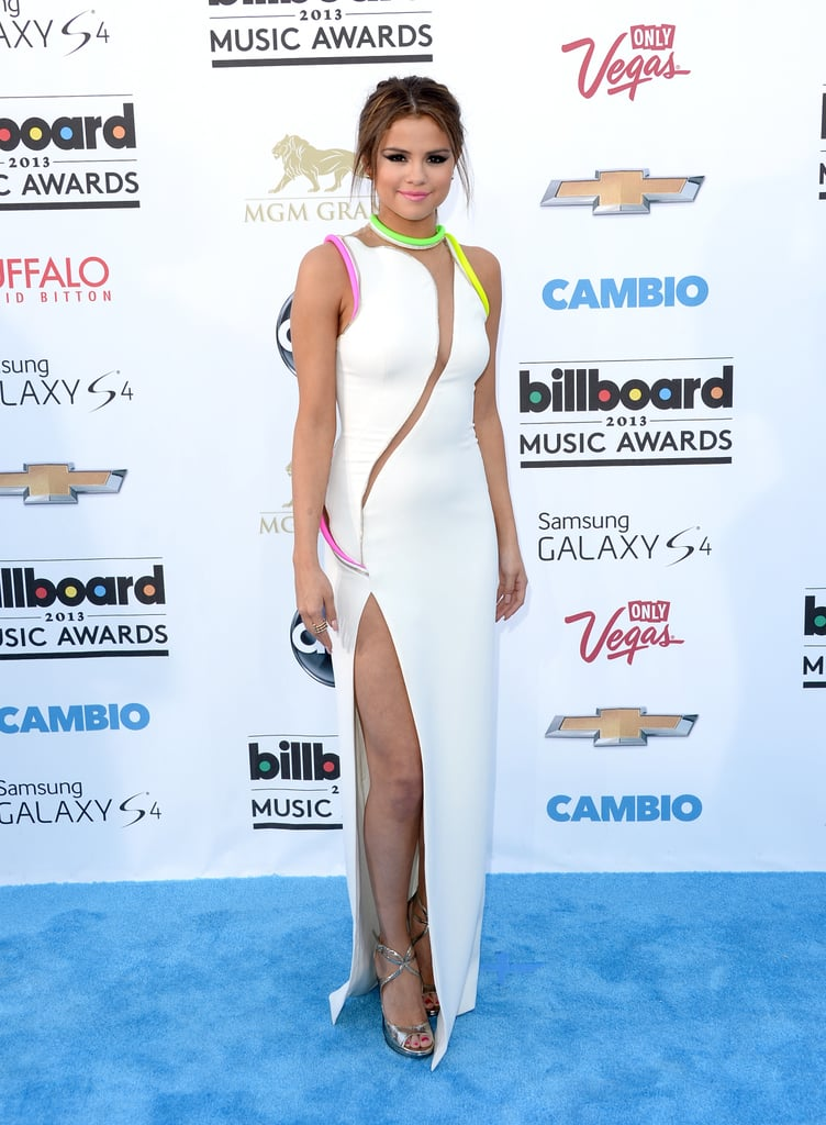 """Selena Gomez showed skin in a sexy white dress with a high slit to hit the blue carpet at the 2013 Billboard Music Awards in Las Vegas today. She's got a big day ahead of her since will take the stage to perform her hit single """"Come & Get It"""" during the show. Selena made headlines last week when speculation arose that she would possibly be seated next to her on-again and off-again beau, Justin Bieber, in the audience during the show. The rumours gathered steam as reports suggested that the pair reunited in Las Vegas ahead of the big award show. Selena and Justin reportedly got cosy at Cirque du Soleil's Love show last night."""