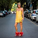 Anna Dello Russo didn't play it safe with her marigold dress. She wore a pair of fuzzy red heels with the mini for a pairing that beckons a perfect street style shot.