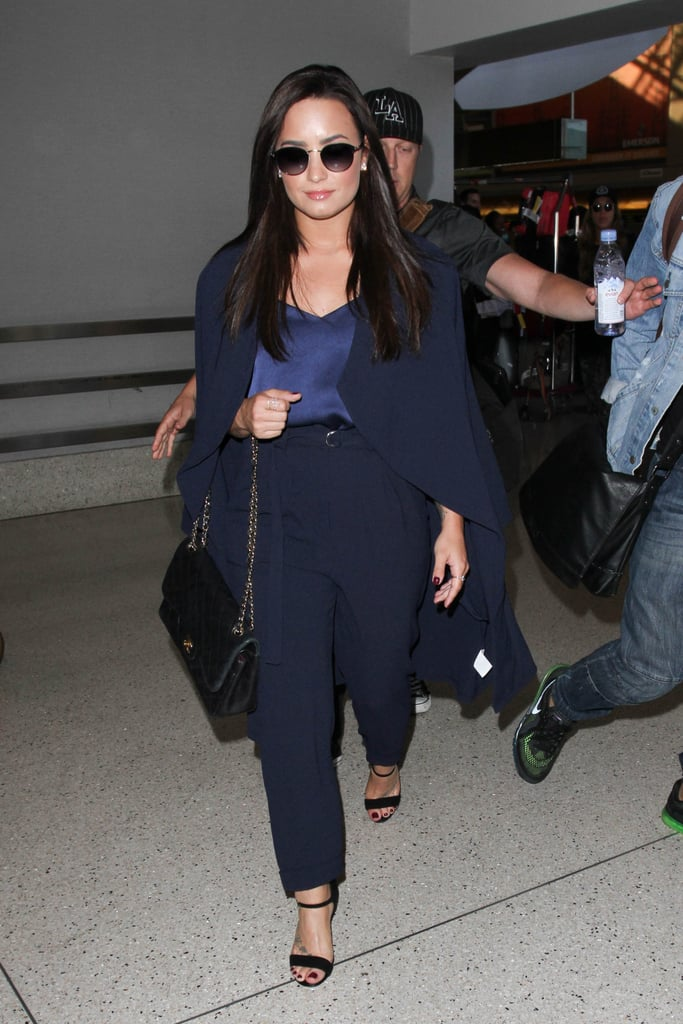 After a gorgeous appearance at Glamour's Women of the Year Awards in New York City, Demi Lovato, who recently confirmed her relationship with Luke Rockhold, journeyed back to the West Coast in style. The singer arrived at LAX wearing a monochrome navy travel outfit — high-waisted trousers, a silk cami, and the chicest cape coat — that certainly puts the sweats and a t-shirt vibe to shame. She even wore heels! Take a queue from Demi and wear a comfy yet stylish outfit to go from the airport to dinner with family this holiday season. See Demi's very on-trend ensemble in action, then admire even more of her 2016 style.      Related:                                                                                                           15 Presents For the Confident Demi Lovato Fan