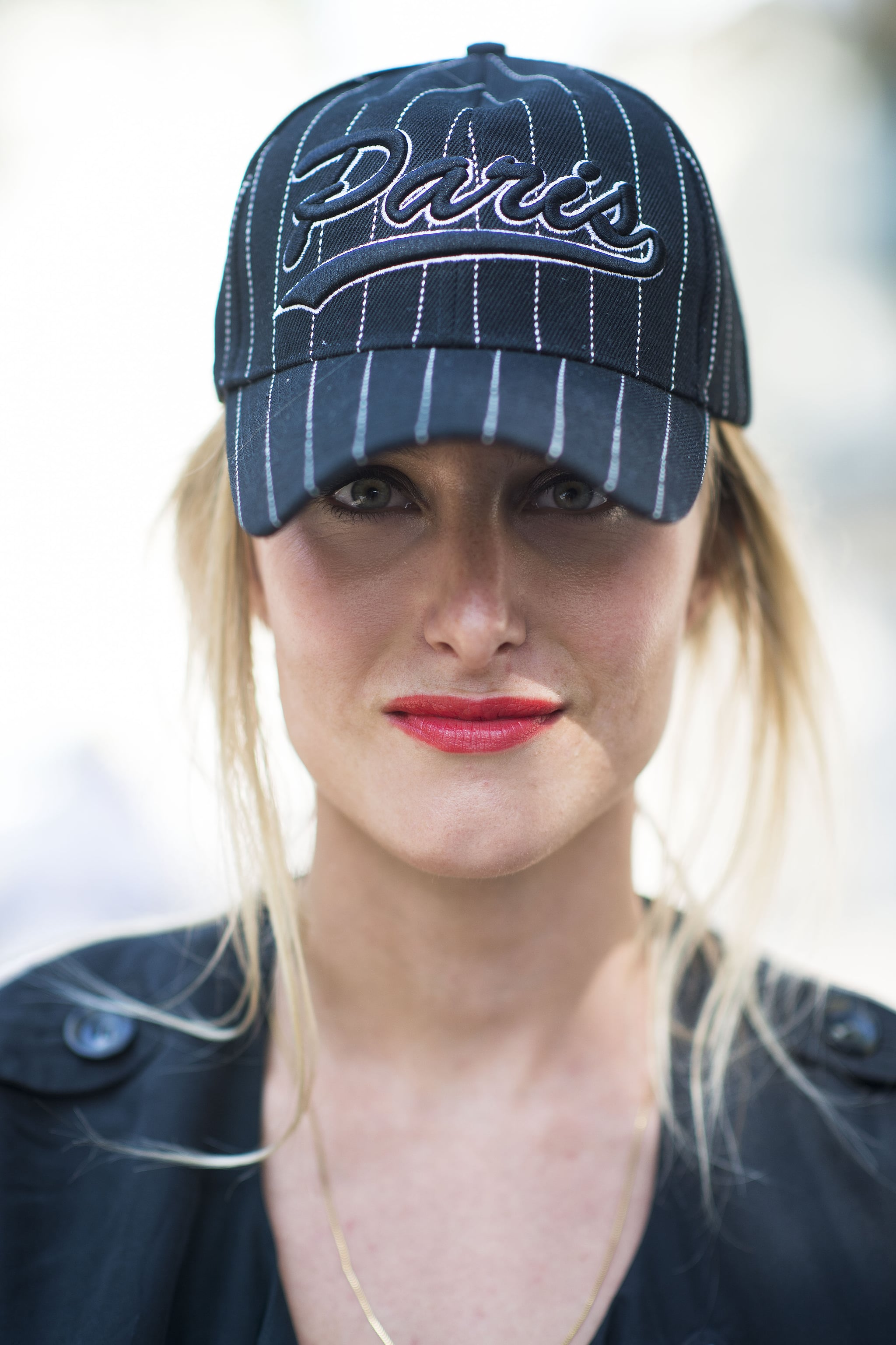 There is no confusion which team this showgoer is on, and the coral lipstick adds femininity to a simple baseball cap.  Source: Le 21ème | Adam Katz Sinding