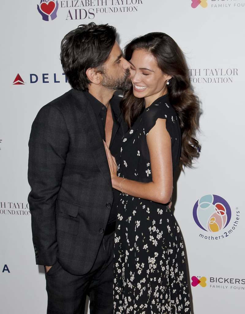 John Stamos and Caitlin McHugh look like they're on cloud nine after announcing their engagement earlier this week. On Tuesday, the couple flaunted their love when they attended the mothers2mothers and The Elizabeth Taylor AIDS Foundation Benefit Dinner in Beverly Hills. Aside from John planting a few sweet kisses on Caitlin, she also made sure to show off her gorgeous ring for the cameras as she rested her hand on the Fuller House actor's chest.  While the couple has been somewhat private about their relationship since they got together in 2016, we do know one crucial detail about their romance: they love Disney. Earlier this year, the pair dressed up as Ariel and Prince Eric during a trip to Disneyland, and John actually made a video of romantic moments from Disney and Pixar animation for his proposal. How charming!       Related:                                                                                                           Solid Proof That John Stamos Gets More Good-Looking With Age