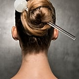 While the models didn't actually wear this giant hair pin while walking down the runway for Pamella Roland, it's still a great way to keep your hair in this twisted bun IRL, although there's no need to use such a statement accessory like the one pictured. Instead, use any lengthy pin (even a chopstick could work!) to pull your hair into a ponytail, twisting it until it begins to spin into a ballerina-bun shape and securing it with a pin. As a bonus, with your hair folded up into itself like that, you'll be setting yourself up for the perfect bun drop video (if you feel so inclined).