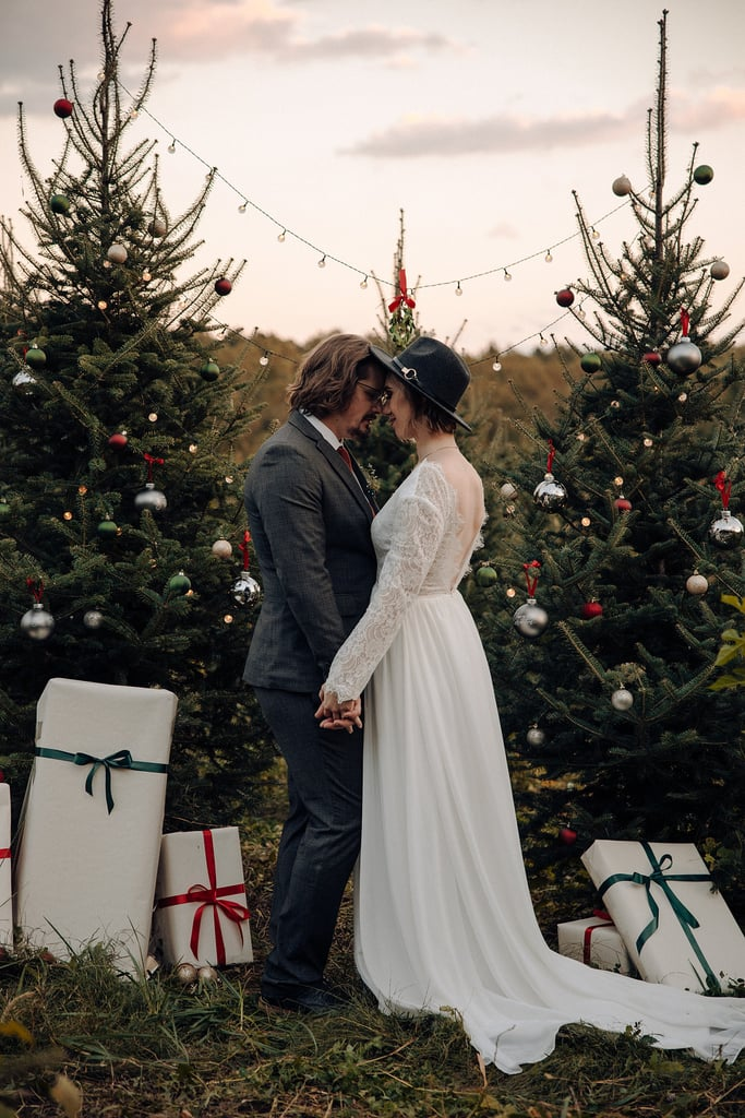 "In 2019, Taylor Swift came out with the whimsical, romantic, and perfectly seasonal song ""Christmas Tree Farm."" Her music video featured old footage from when she was younger: joyfully playing in the snow, decorating her home for the holidays, and, as the song would have it, picking out an evergreen from a Christmas tree farm. The holiday motifs and romantic lyrics inspired photographer Madeleine Boudreau to bring the song to life and plan a Christmas-themed wedding shoot with recently engaged couple Clair and Martin. Set in a sea of evergreens in Glenelg, MD, the styled ceremony was held at the TLV Tree Farm, a family-owned and operated establishment that has been around for more than 100 years.  The shoot intertwined both Christmas themes and Taylor's lyrics, and featured everything from a rustic apple cider bar to trees that were adorned in the holiday's best decor. ""All stations — from the cake table and cider bar to the sweetheart table and altar — were designed and decorated with eclectic items, all personally made or found second hand,"" Boudreau wrote on her website. The sweetheart table was inspired by the rustic nature of a farm, but was enhanced to capture a new level of elegance by including rich greenery and chic table settings. The bride-to-be's overflowing bouquet incorporated the traditional Christmas colors of green and red along with captivating eucalyptus leaves and crimson flowers.       Related:                                                                                                           Here's All the Inspiration You Need to Have the Winter Wonderland Wedding of Your Dreams               With nods to the enchanting holiday song found in every nook of the farm — from the hot apple cider bar tucked away between the trees to the mistletoe hanging at the altar — this styled wedding shoot was merry, bright, and in every way romantic. Take a look at the special moments from the shoot ahead, and let these holiday lyrics captivate you for Christmases to come: ""In my heart is a Christmas tree farm / Where the people would come / To dance under sparkling lights / Bundled up in their mittens and coats / And the cider would flow / And I just wanna be there tonight.""      Related:                                                                                                           This Couple's Lake Tahoe Winter Wedding Showcased Nature at Its Best"