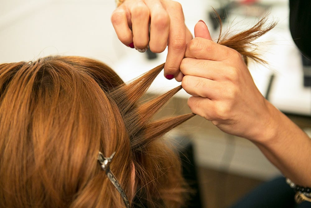 Starting with a section of hair from behind one ear, separate it into three strands.