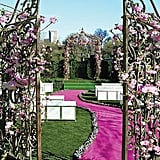 Wrought-iron gates covered in flowers and a bold, winding aisle set the tone for a romantic wedding celebration.