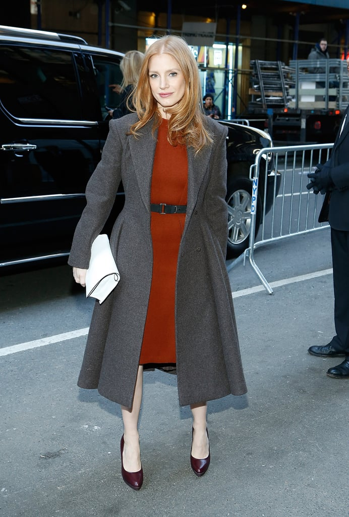 Jessica Chastain headed to the Calvin Klein show in an orange-red sheath dress, purple patent pumps, a gray coat, and a white clutch.