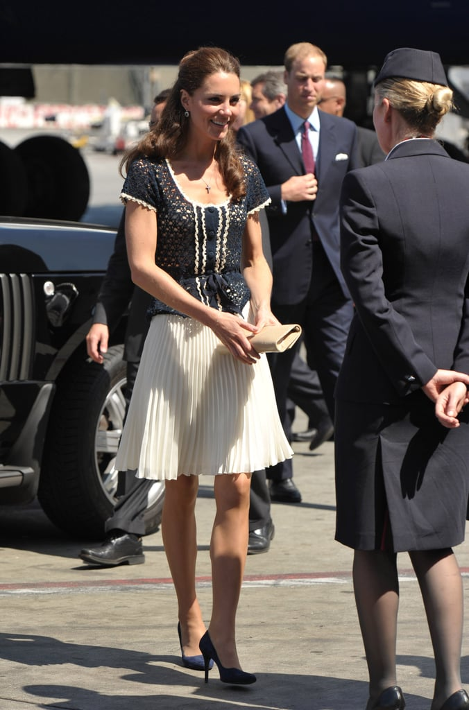 July 10th, 2011 At LAX, ready to depart for the UK.   Kate wore a navy crochet top from Whistles and a Whistles Lina Dobby pleated skirt. She paired the look with an eggshell envelope clutch and navy pumps.