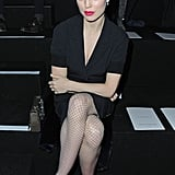 Melissa George sat front row at Nina Ricci wearing all black — a skirtsuit with fishnet tights and cutout pumps — with a pop of hot-pink lipstick.