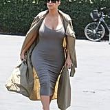 Kim chose a ribbed grey midi dress, long parka, caged Jimmy Choo heels, and dark sunglasses.