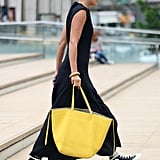 Add a bold pop of color, by way of a canary yellow tote, to an all-black dress.