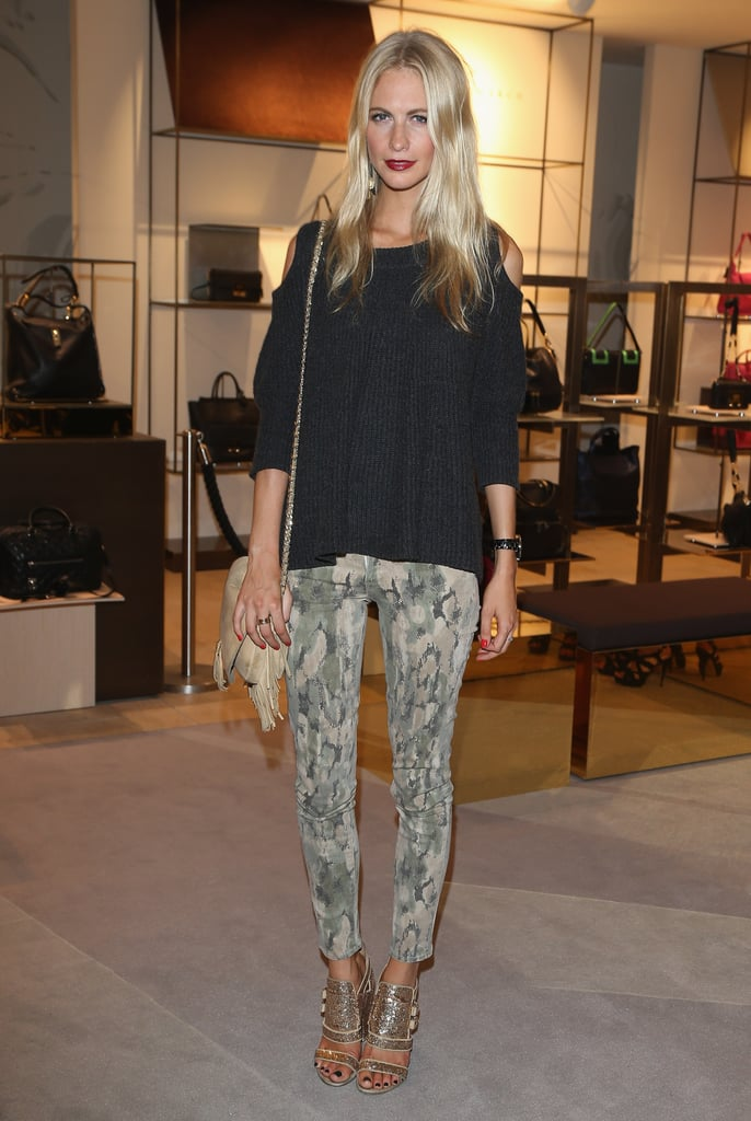Poppy Delevingne opted for a cool-girl take on eventwear in a pair of printed pants and gold heels at a store opening in Berlin.