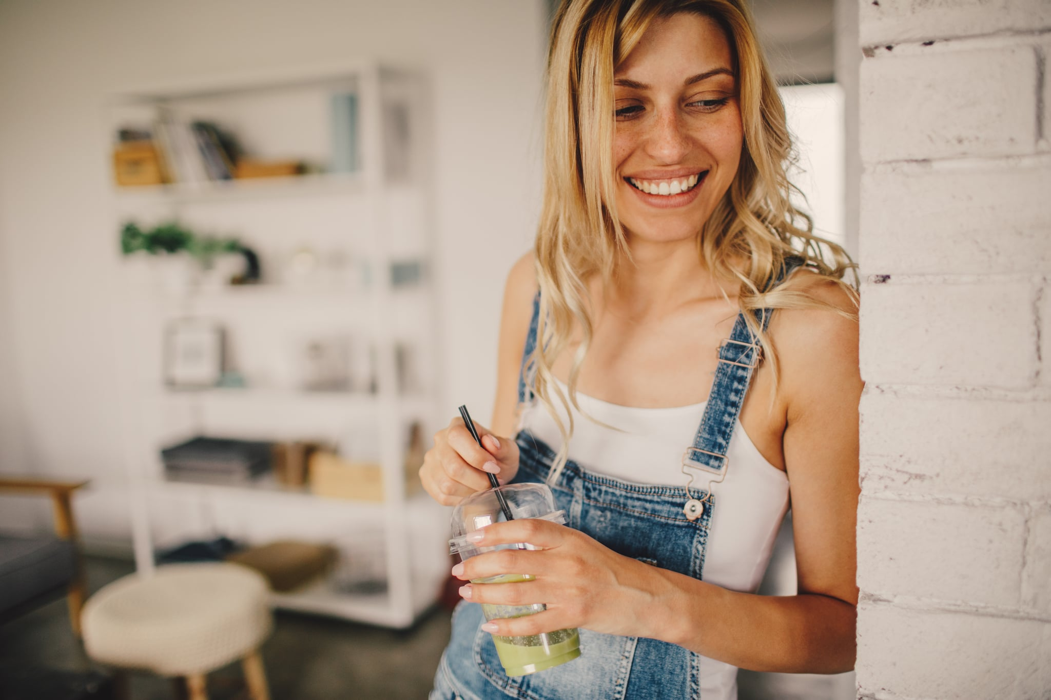 Photo of a young smiling woman having healthy smoothie for a snack meal