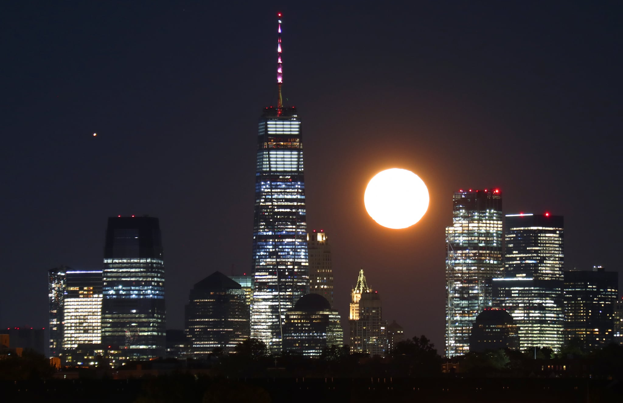 NEWARK, NJ - OCTOBER 2: The moon rises along with Mars behind lower Manhattan and One World Trade Center in New York City, a day after the full Harvest Moon on October 1, 2020 as seen from Newark, New Jersey. (Photo by Gary Hershorn/Getty Images)