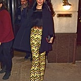 Amal paired her shimmering, chevron printed high-waist pants, from Giambattista Valli's pre-Fall 2015 collection, with a furry, bow-adorned crop top. The gold finish of her box clutch and her dangling earrings played up the yellow in her flares, and her chic black coat topped off her look.