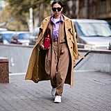 Wear Your Trench Coat Over Your Shoulders and Style It With Sneakers