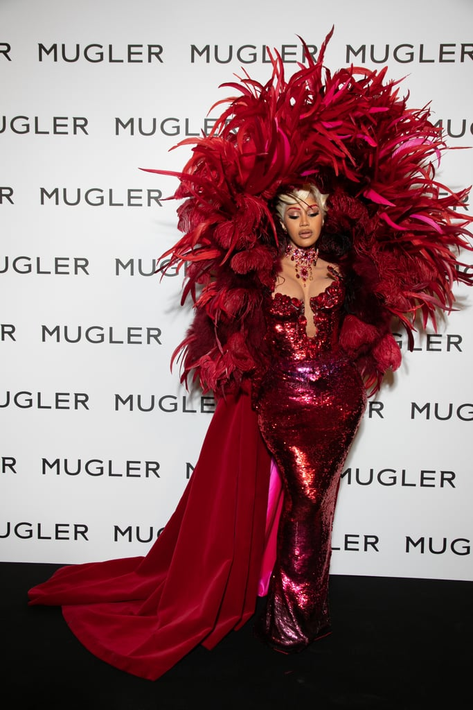 """Cardi B just set the bar for grand entrances at Paris Fashion Week this year, and it's shrouded in red feathers and enough glitter to light up a Las Vegas stage. On Sept. 28, Cardi attended the Mugler fashion show and made her first public appearance since giving birth to her second child earlier this month. Dressed to the nines, the """"WAP"""" singer held nothing back in a fitted red sequin dress with a low-cut sculptural neckline. But the true pièce de résistance was her flowing red cape adorned in thousands of scarlet feathers. Like a headpiece and shawl in one, the luxurious cape framed Cardi's Old Hollywood hairstyle and figure-hugging gown in a way that made it hard to tear our eyes away from the extravagant look. Kicking the sparkles up a notch, Cardi accessorised with matching sequin evening gloves, a glistening chandelier necklace, gemstone earrings, and vibrant red eyebrows dripping in almost as much glitter as her dress. No matter which way she turned, the feathers and glitter made it clear that Cardi was the showstopper at this event. With Paris Fashion Week still underway, we hope to see even more looks as spectacular as Cardi's. See her dress — reminiscent of her Thom Browne look at the 2019 Met Gala — and lavish cape from all angles here.      Related:                                                                                                           Prepare to Fall in Love With Jake Gyllenhaal and His Pale Pink Prada Tuxedo"""
