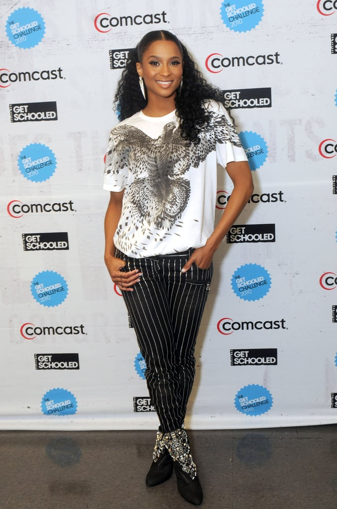Ciara does funky in striped pants, a bold tee, embellished boots, and spear earrings.
