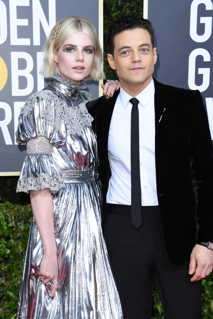 Fans may have said goodbye to Rami Malek's Elliot after the Mr. Robot finale, but Rami isn't going anywhere. On Sunday, the actor hit the red carpet for the Golden Globe Awards alongside his stunning partner and former Bohemian Rhapsody costar Lucy Boynton.  Rami and Lucy scored nominations for Mr. Robot and The Politician respectively, and they worked the red carpet like the power couple they are. If you ever thought velvet or metallics were going out of style, this duo has several words for you (and they're all incredibly chic). Scroll on to see more photos from the couple's night ahead.