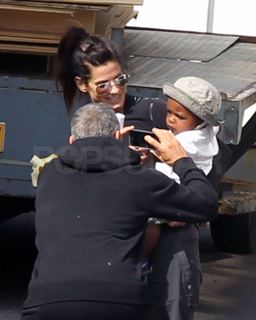 George Clooney joined his Gravity costar Sandra Bullock and her adorable little guy, Louis, on the set of the film in London yesterday. The actor used his iPhone to capture some pictures of the supercute tot, who looked precious in a wide-brimmed hat, and chatted with Sandra. George might not have any kids of his own, but he does play a dad in the upcoming The Descendants, and he seemed to have an easy time tapping into his paternal side around Louis. Sandra is back to work after taking some time off during her son's infancy. She just started working with George on the drama about a space-shuttle disaster and recently wrapped filming Extremely Loud and Incredibly Close opposite Tom Hanks. Louis has been a frequent fixture behind the scenes on her movies this year, and it's no surprise that the Oscar-winning mother is among your favorite celebrity moms in the 2011 Pop 100.