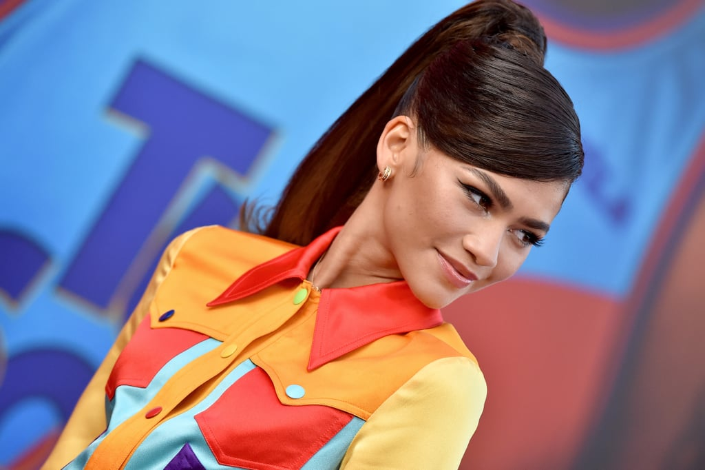 """Zendaya isn't quite done being Lola Bunny. The actress attended the Space Jam: A New Legacy premiere in Los Angeles on July 12 wearing a look inspired by her character in the sequel. The red carpet appearance joins the many other instances Zendaya and her longtime stylist, Law Roach, took inspiration from style icons and pop culture fixtures. On Instagram, Law wrote, """"Tell me you're Lola Bunny without telling me you're Lola Bunny."""" This particular outfit consisted of a colourblocked jacket and matching shorts from Moschino's recent Resort 2022 collection. Zendaya accessorised with white Christian Louboutin pumps, as well as gold huggie hoop earrings and stacked rings by Bulgari. Though she didn't wear it for the entirety of the red carpet, Zendaya also had in tow a blue face mask with a sparkly basketball on it, which was actually made by her mom, Claire Stoermer. """"Mask courtesy of my mama,"""" she wrote on Instagram Stories.  Take a closer look at Zendaya's bright and bubbly outfit ahead.      Related:                                                                                                           Zendaya Is Lola Bunny! Here's How the Iconic Character Is Changing For Space Jam Sequel"""