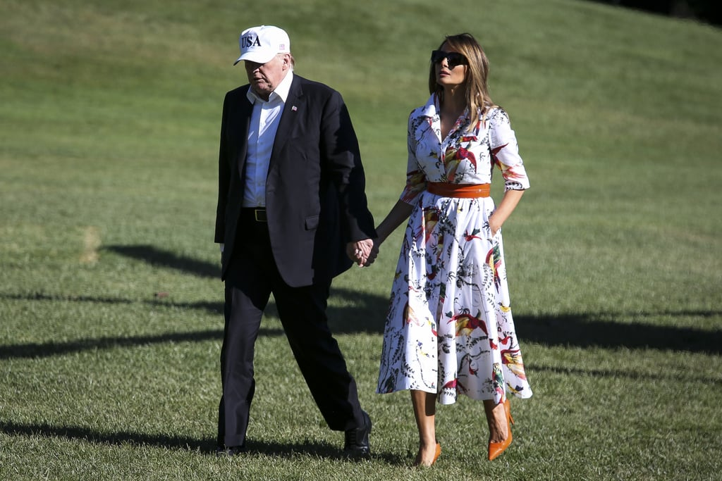 Melania Trump didn't shy away from a bold statement dress during her walk across the South Lawn with President Donald Trump, after returning to Washington DC on July 8. FLOTUS chose a cotton printed midi dress from Erdem for the occasion, pairing the outfit with orange snakeskin Manolo Blahnik pumps, a red belt cinched at the waist, and oversized sunglasses.  The first lady's collared dress usually retails for $1,294 and features colorful birds and plants against a white background. Ahead, see Melania's bold dress from all angles and shop the exact style (it's on sale!) and similar versions for yourself. Related: Keeping Up With Melania Trump's Outfit Controversies Is a Full-Time Job