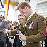 Prince Harry smiled when a little boy gave him a drawing during his visit to the naval base.