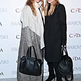 Twinning combo: Cozy coats were the style of choice at the 2015 CFDA announcement party.   Ashley sported a knee-length tuxedo coat in her signature black.  Mary-Kate accessorized her gray floor-length coat with a white scarf.