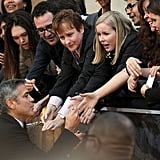 George signs autographs for fans at the Oscars.