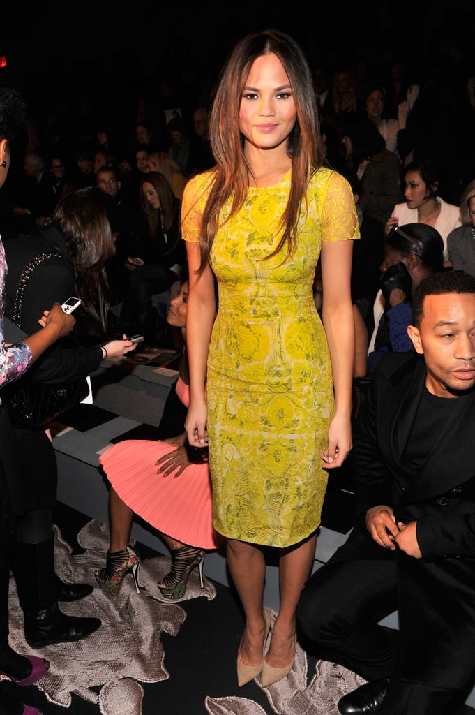 Chrissy Teigen lit up the front row of Vera Wang in her bright yellow printed dress.