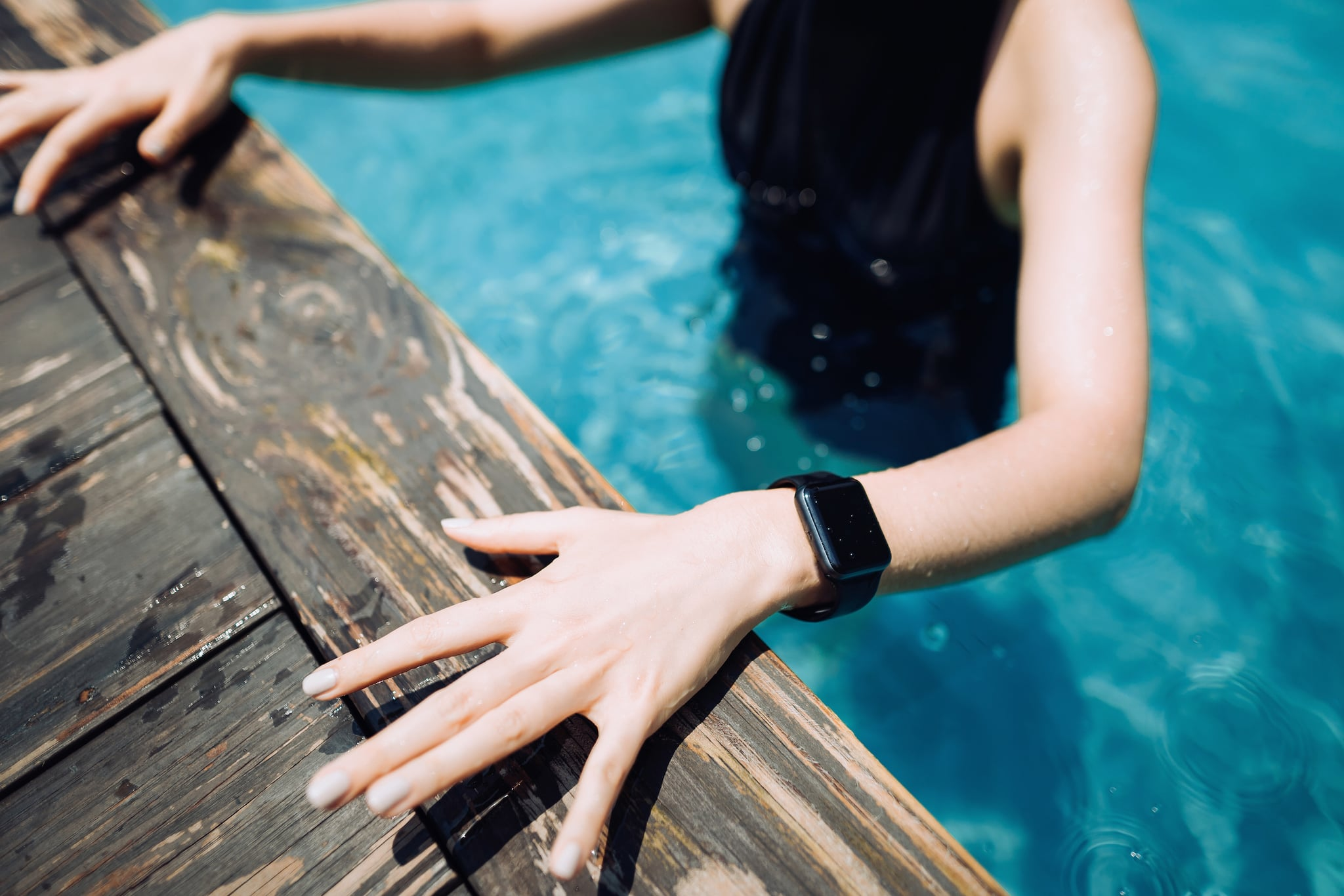 Close up of young female swimmer with smartwatch getting out from swimming pool