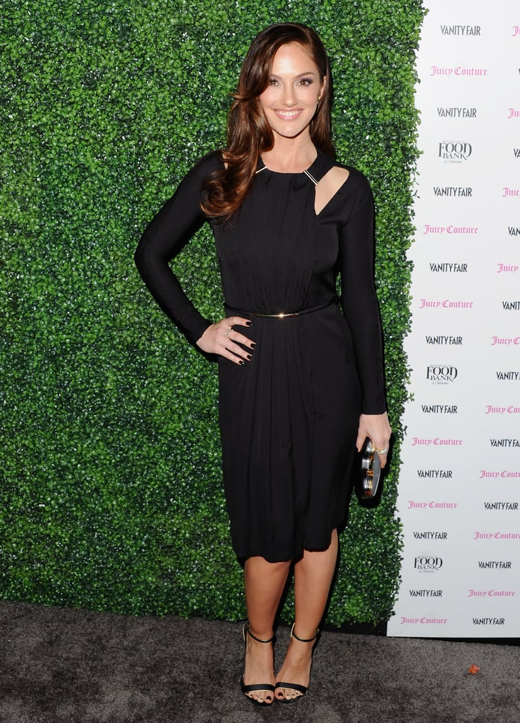 Minka Kelly showed off a cooler take on LBD styling at the Vanity Fair Vanities Calendar party, opting for a long-sleeved sheath complete with a cutout neckline. To finish, she kept her hair long and wavy, then accessorized with minimalist-cool sandals, a metallic gold waist belt, and a metallic silver minaudiere.